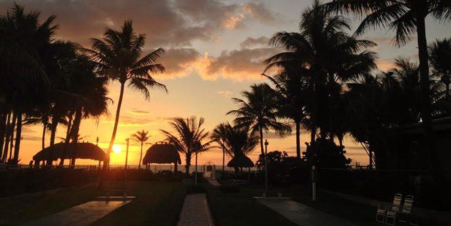 Photo of sunrise with orange sky fading to light blue.